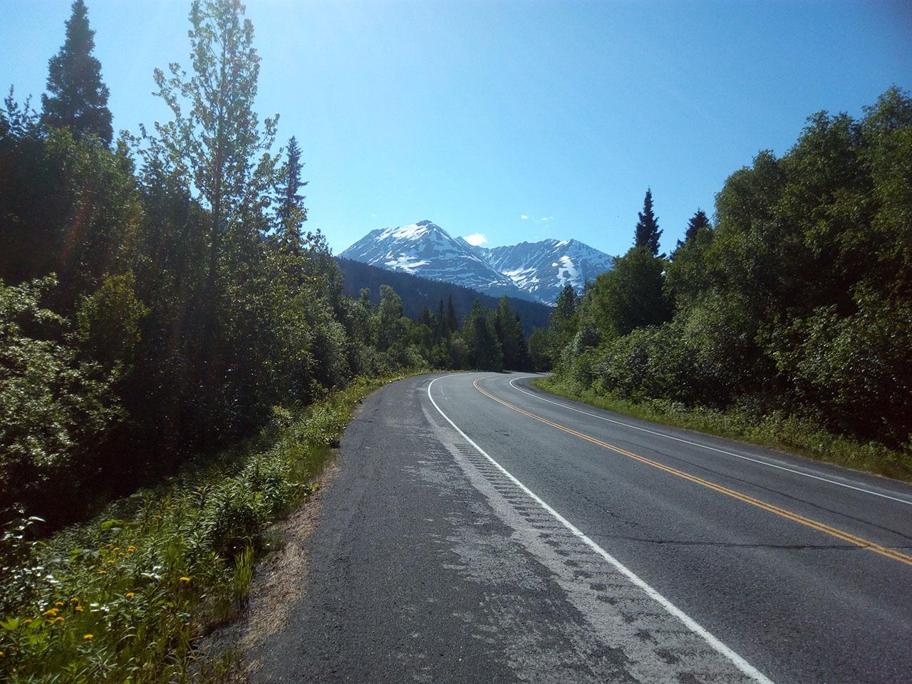 Paved road and Alaska mountains.