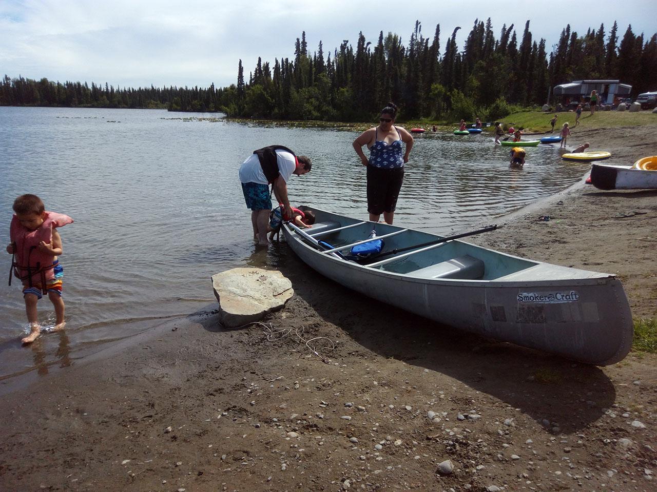 Canoers on river shore.