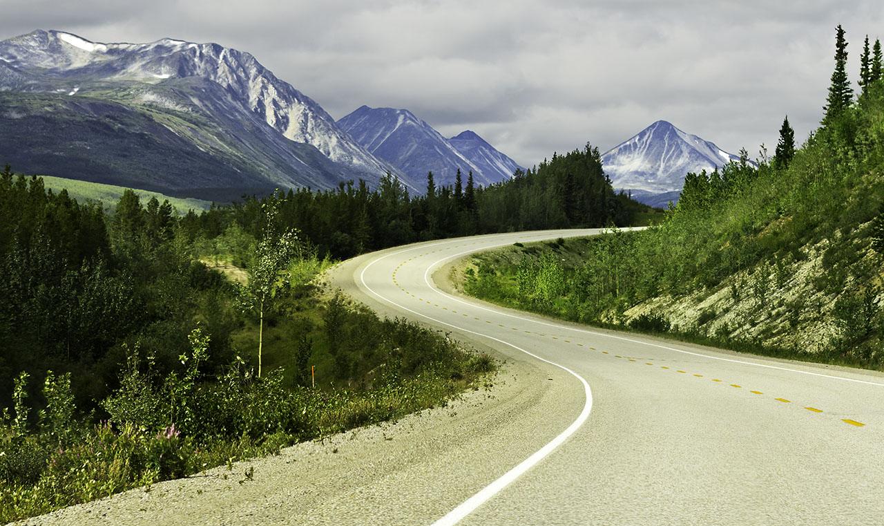 Curved asphalt road in high mountains of Alaska